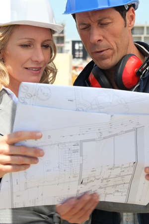female architect and workman consulting blueprints in construction site photo