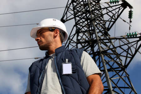 telephone pole: Worker standing in front of an electricity pylon