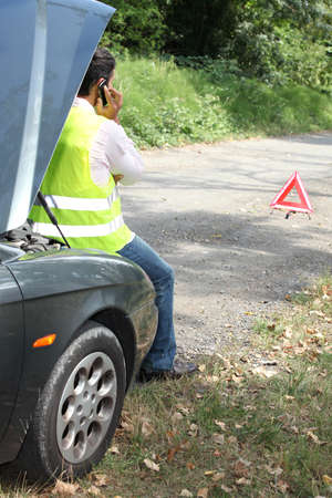 Man sat by car waiting for roadside assistance photo