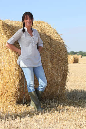 Woman in wellington boots standing in a field of hay photo