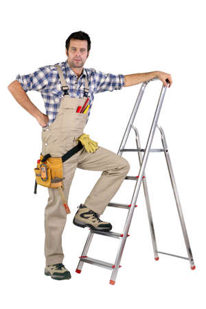 journeyman technician: Handyman stood by step-ladder Stock Photo