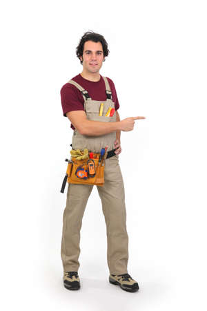 hands on hips: Handyman pointing at a blank space Stock Photo
