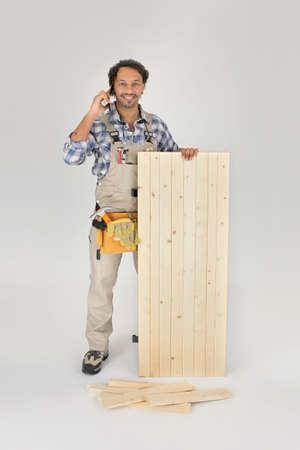 Carpenter stood with wooden door photo