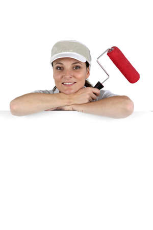 Woman stood by blank poster with paint roller photo