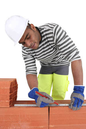 A bricklayer using a ruler photo
