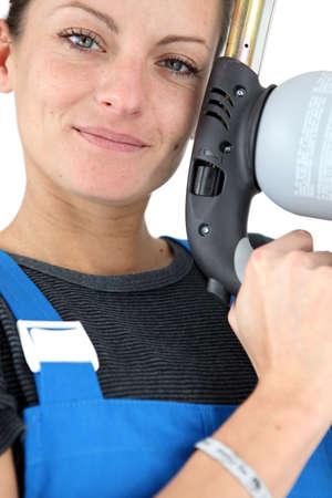 dishy: beautiful craftswoman holding a welding torch