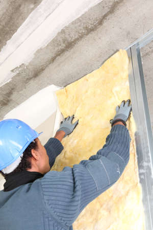 insulating: Man insulating wall