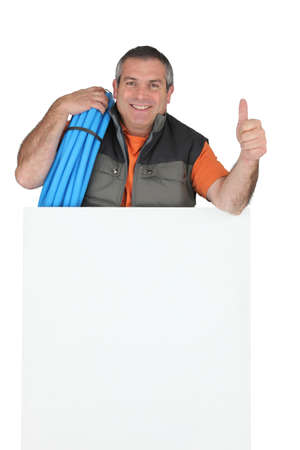 stood up: Manual worker stood behind blank message board Stock Photo