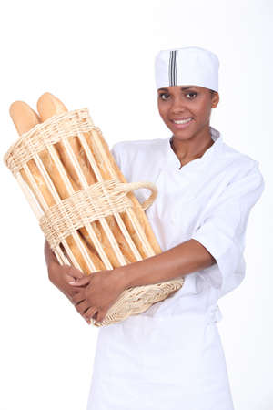 A baker holding a basket of bread photo