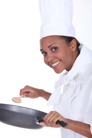 Female chef in uniform with a deep frying pan and wooden spoon photo