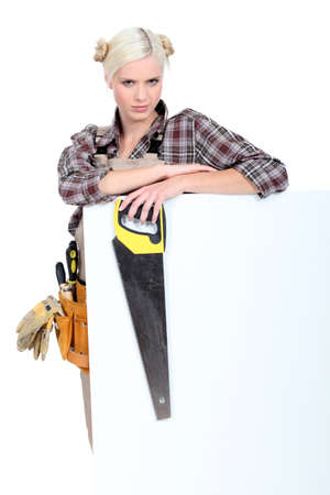 Woman with a tool belt, a saw and a blank board photo