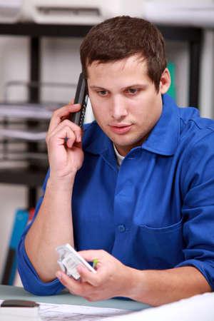 tradesman: Electrician checking a part over the phone Stock Photo