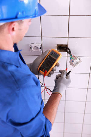 voltmeter: Electrician with a voltmeter