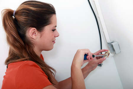 disconnecting: Female electrician installing a power point
