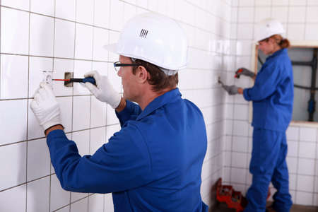 skilled labour: Two electricians working in public rest room Stock Photo