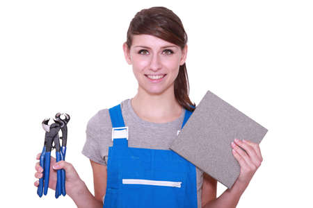 Woman holding tile and tile cutter photo