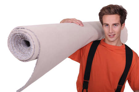 carpeting: Man carrying a rolled-up carpet