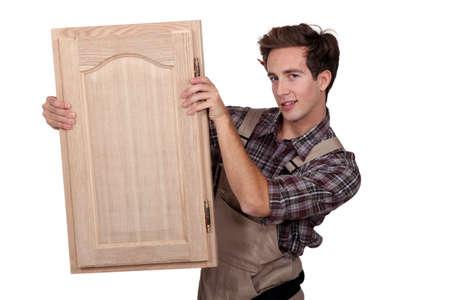 closet door: A carpenter holding a closet door