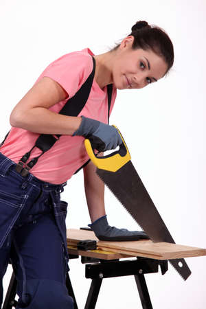 tongue and groove: Young woman sawing a wooden board Stock Photo