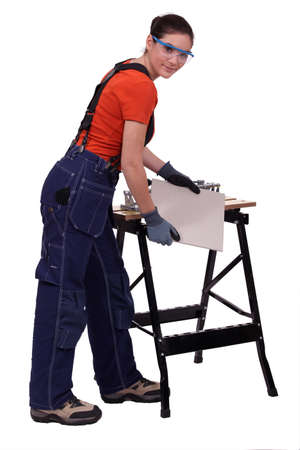 square ruler: Woman cutting tile Stock Photo