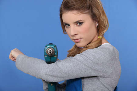 Girl with drill on blue background photo