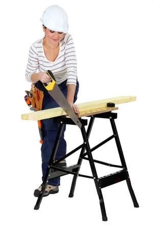 Woman sawing wood on work-bench photo