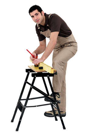 carpenter making measurements with pencil on lumber strip against studio background photo