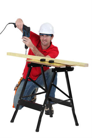 Man drilling through plank of wood Stock Photo - 15095459