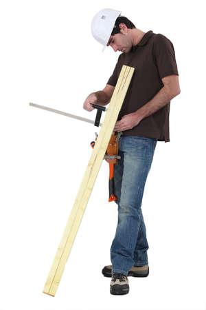 obrero trabajando: Tradesman pegar dos tablas de madera junto