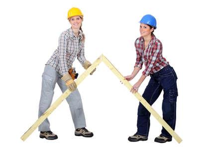 tradeswomen: Tradeswomen building a frame