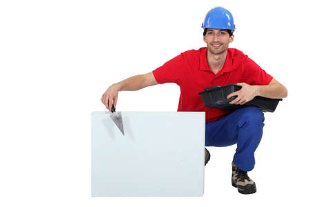 hunker: portrait of attractive bricklayer hunkering down with trowel and copyspace