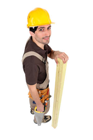 2x4 wood: Builder with wood and saw