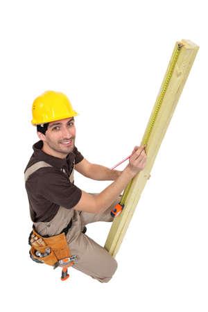 anticipate: Craftsman  measuring plank of wood