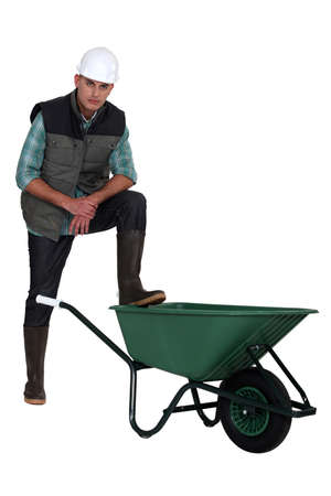 poker faced: Tradesman with his foot propped on a wheelbarrow Stock Photo