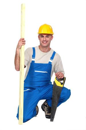 serrucho: Hombre con una sierra de mano y un trozo de madera