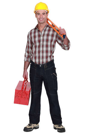 sturdy: Construction worker holding a toolbox and spirit level Stock Photo