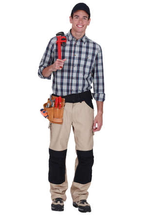 baseball hat: Clean-cut tradesman holding a pipe wrench Stock Photo
