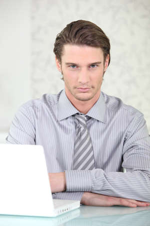 Man wearing shirt and tie sat with laptop photo