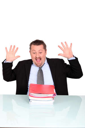 pressured: Man shocked at his pile of paperwork Stock Photo