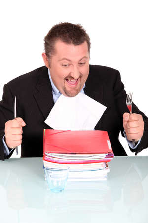 devour: Man about to devour a pile of files Stock Photo