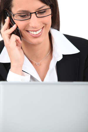 wearer: Smiling young woman talking on a cellphone while using a laptop computer Stock Photo