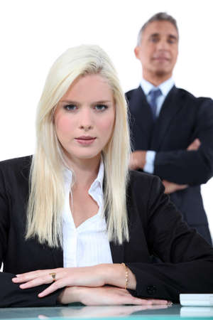 younger: Young blonde businesswoman with older man in the background Stock Photo