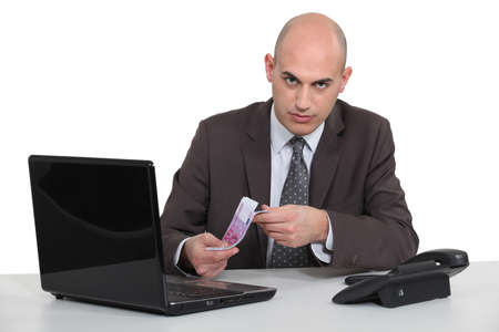 Businessman with a laptop and Euros photo