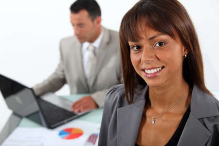 enterprising: Smiling businesswoman standing in front of a colleague and his laptop