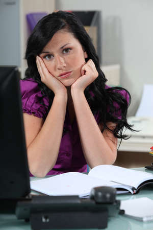 Bored secretary at her desk Stock Photo - 15124935