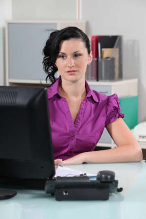 tertiary: young brunette secretary in office Stock Photo