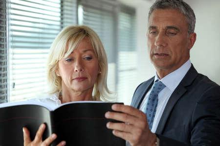 senior business: Senior business couple reading through contract