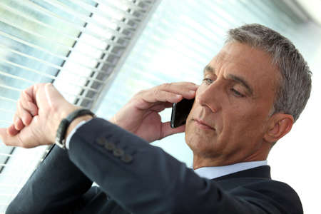 looking at watch: Businessman looking at his watch whilst on the phone
