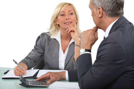 Mature business couple at a desk with a calculator
