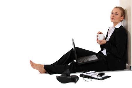 Barefoot businesswoman sat with coffee and laptop photo